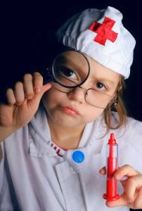 Child playing doctor with hypodermic needle